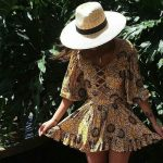 Sunflower-patterned cross-stitch sundress paired with a wide-brimmed hat.