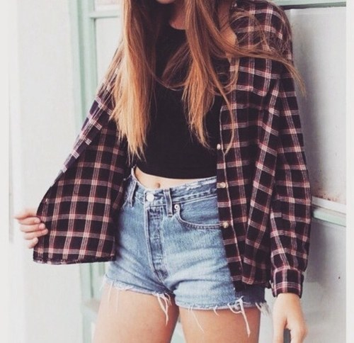 White crop top paired with cut-off shorts and a tie-around red and black flannel.
