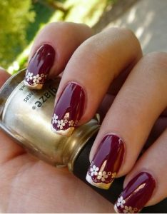 Burgundy Nails with Gold Floral Detail